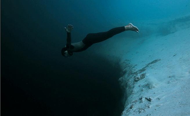 nageur sous marin qui plonge dans un trou noir